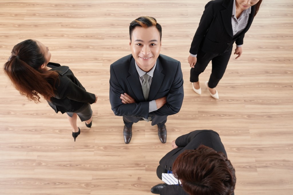 Directly above view of cheerful Vietnamese entrepreneur standing in office with arms crossed and looking at camera, his male and female colleagues passing by
