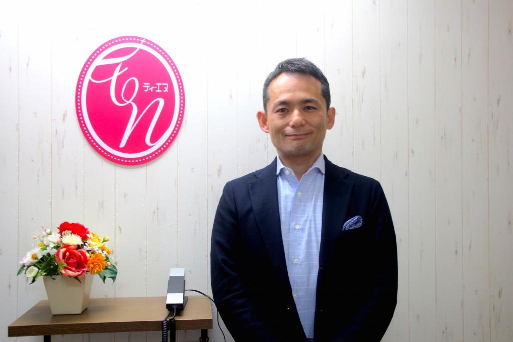 株式会社ティエヌの代表取締役社長山口親太さんと会社ロゴ